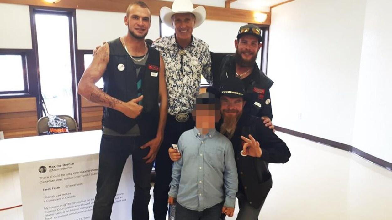 Maxime Bernier pose aux côtés de trois hommes vêtus de vestes affichant Northern Guard, ainsi qu'un enfant au visage brouillé pour protéger son identité.