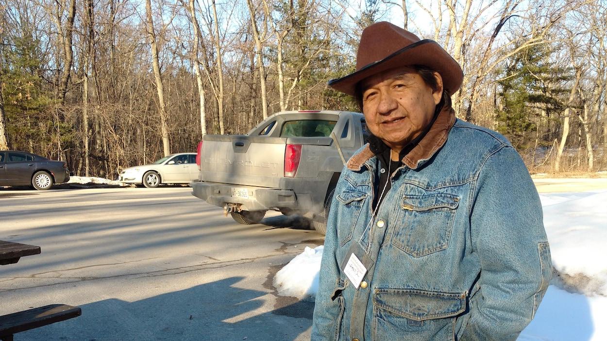 Vêtu d'un chapeau de cowboy brun et d'une veste en denim, il occupe le stationnement à l'entrée du parc.