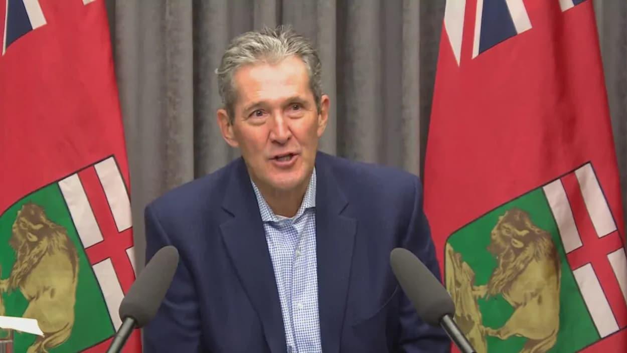 Brian Pallister, devant deux microphones et des drapeaux provinciaux.