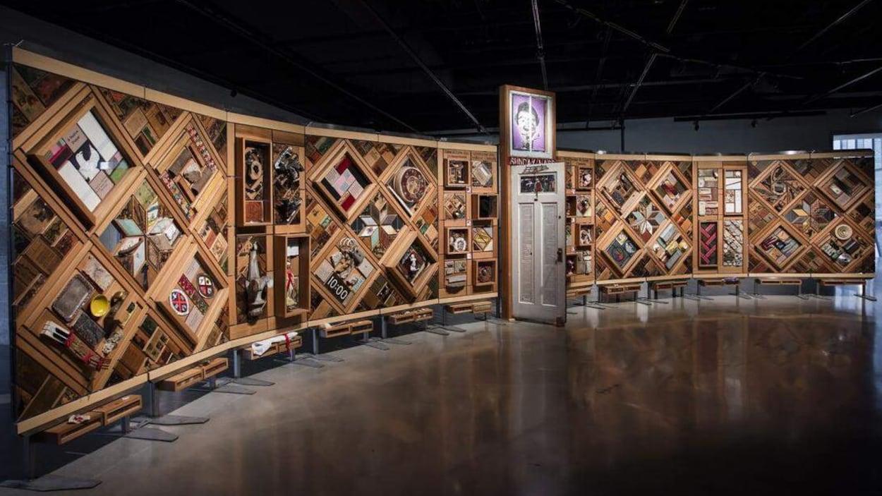 Une grande oeuvre d'art formée de cadres de bois et d'objets rappelant l'histoire des pensionnats autochtones.