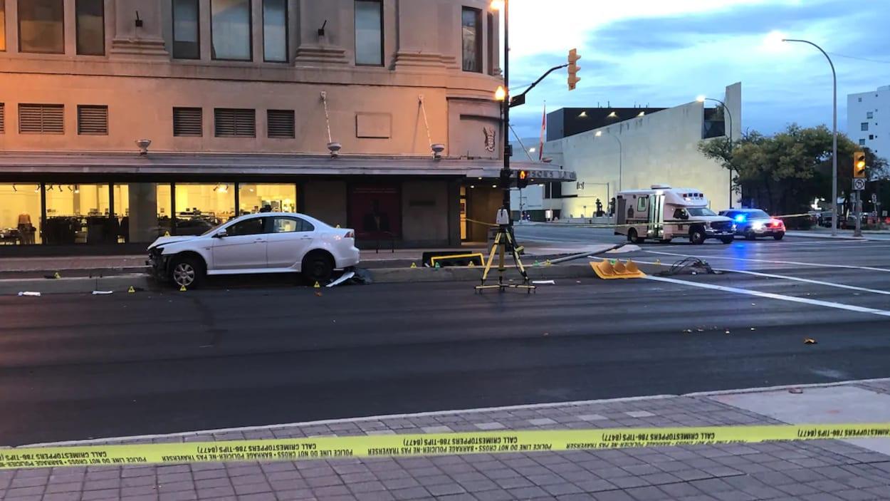 Une voiture accidentée à cheval sur un bloc de béton près d'une intersection.