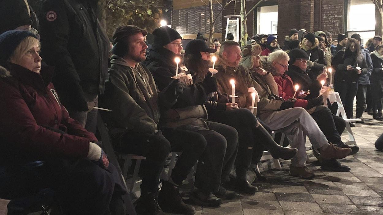 Des gens assemblés près d'une église font une veillée à la chandelle pour commémorer les victimes du présumé tueur en série Bruce McArthur.