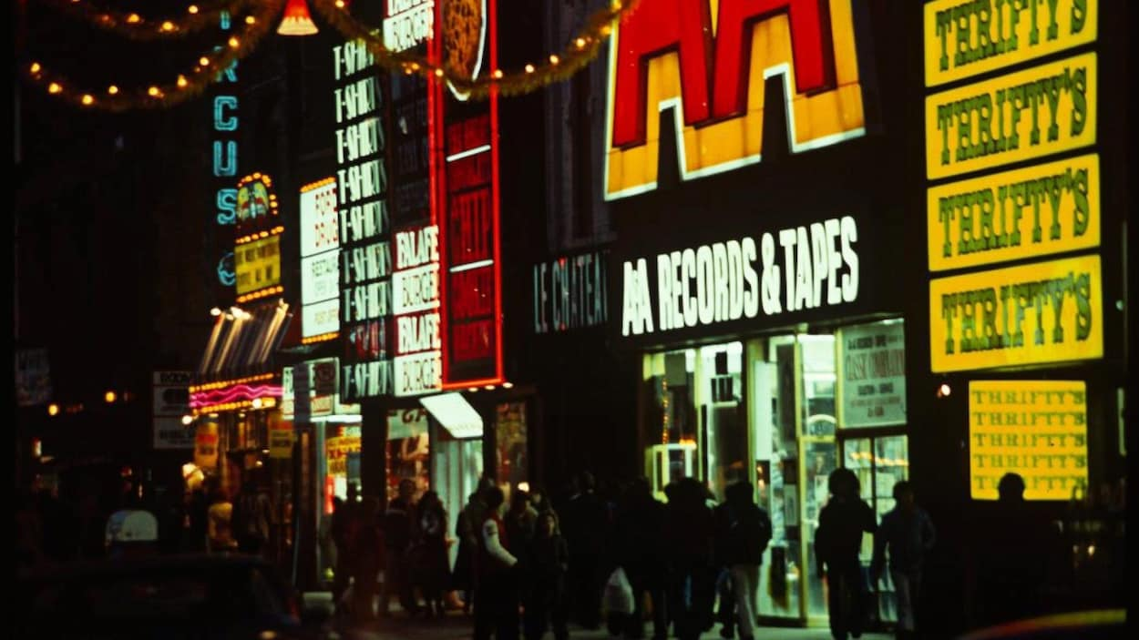 Photo d'une rue la nuit avec des gens qui marchent sur le trottoir sous des enseignes rouges et jaunes de magasins.