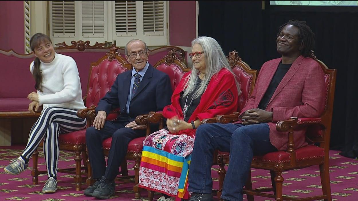 Quatre personnes assises côte à côte sur des chaises au Salon rouge de l'Assemblée nationale.