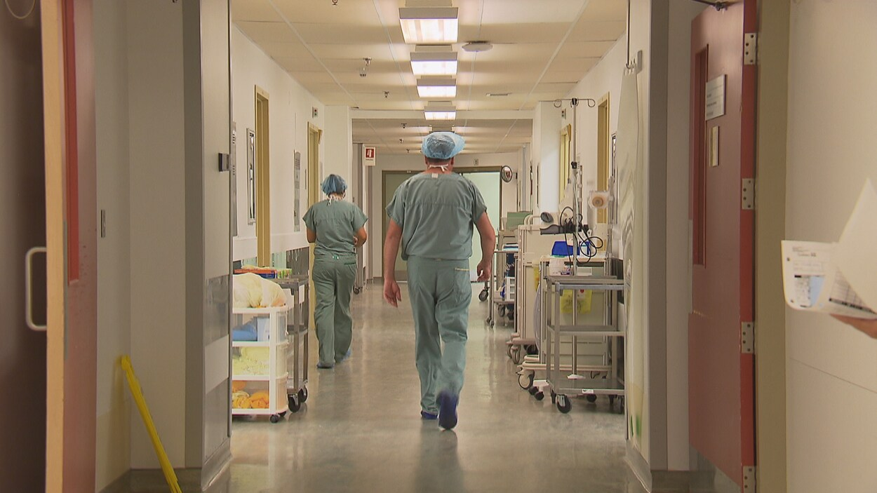Un médecin marche dans un corridor d'hôpital