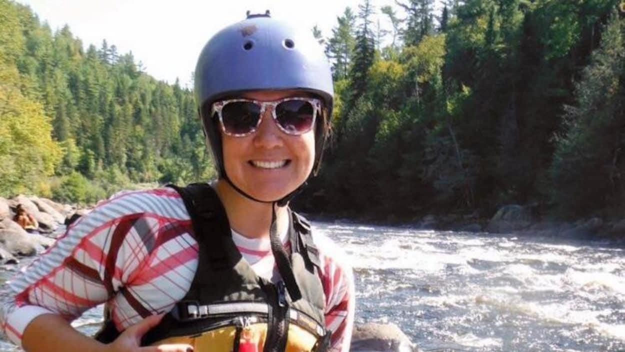 Une femme souriante devant une rivière.