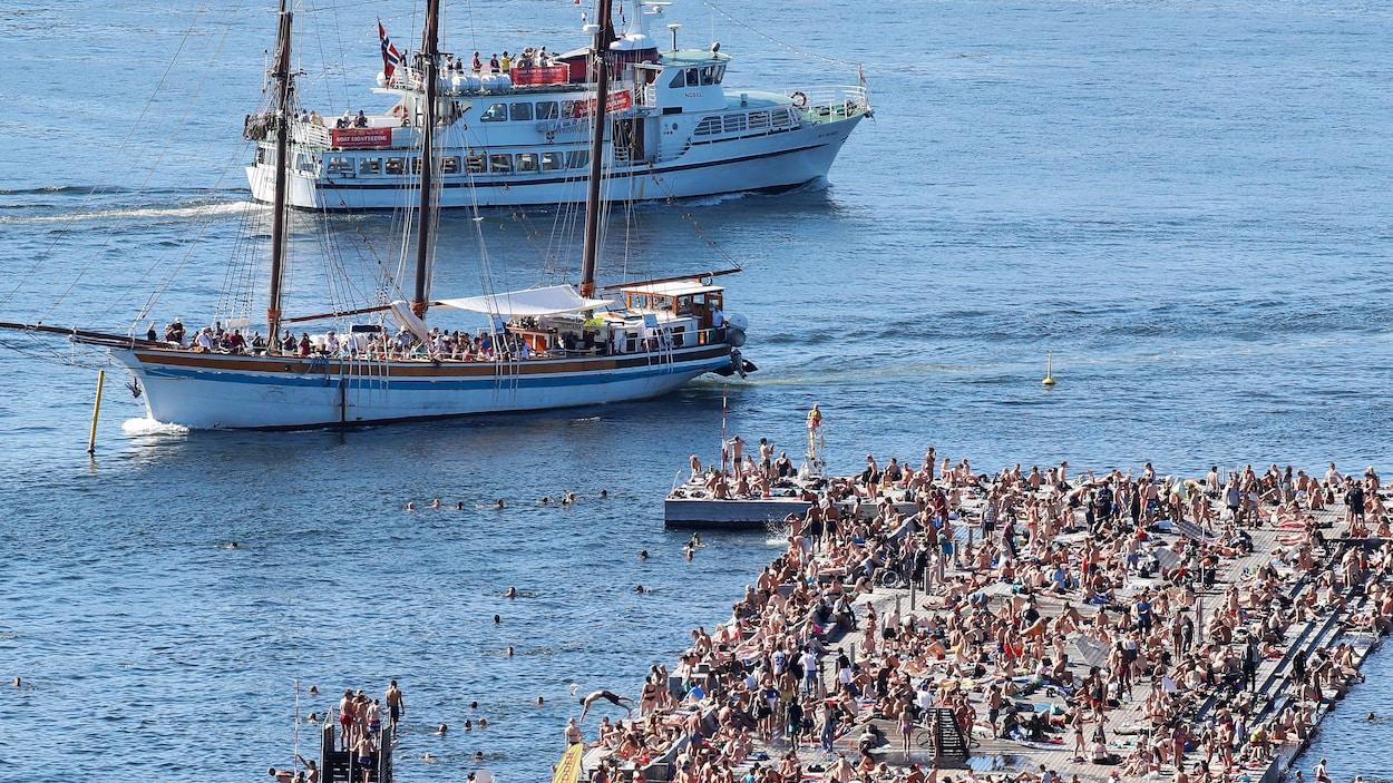 Une plage publique bondée de monde en Norvège où un grand voilier et un bateau de croisière sont visibles.