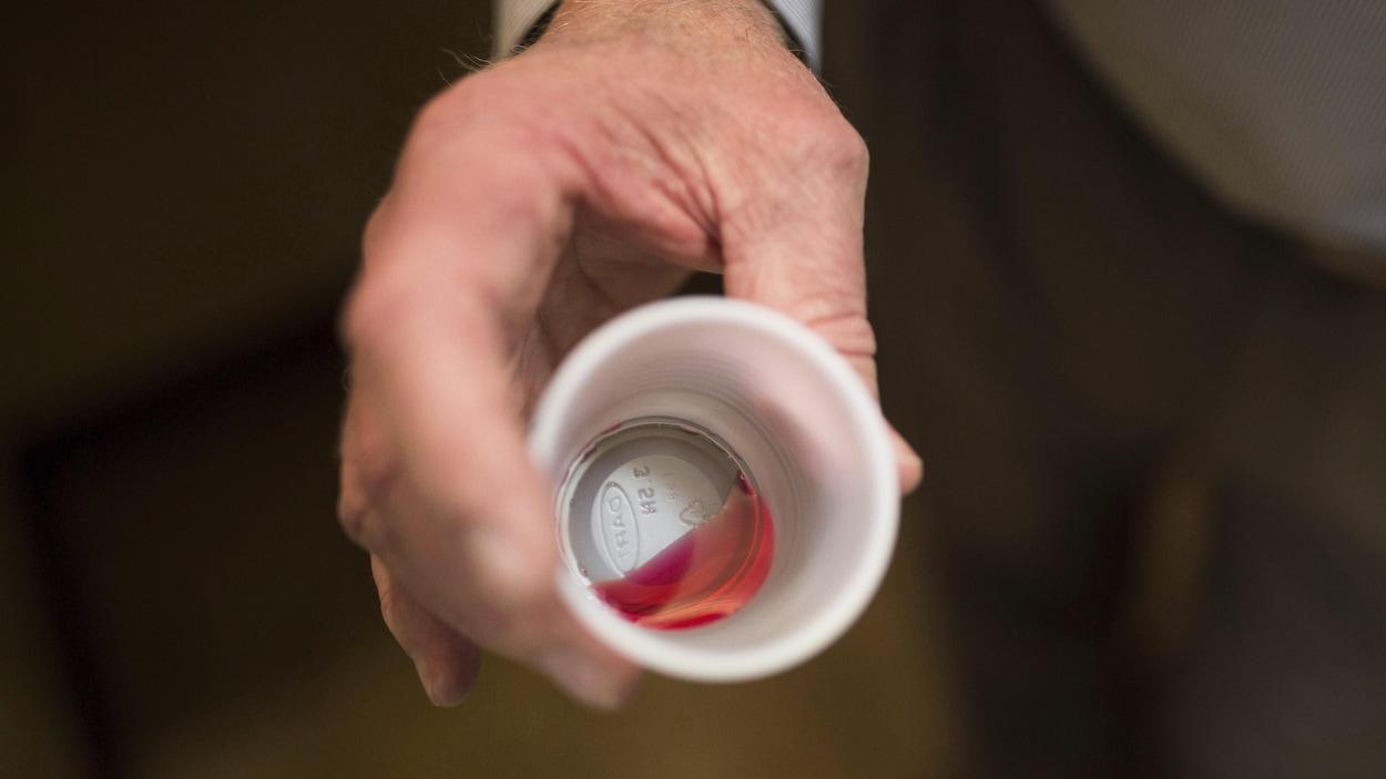 Un liquide rouge qui représente 35 mg de méthadone dans un gobelet de plastique.