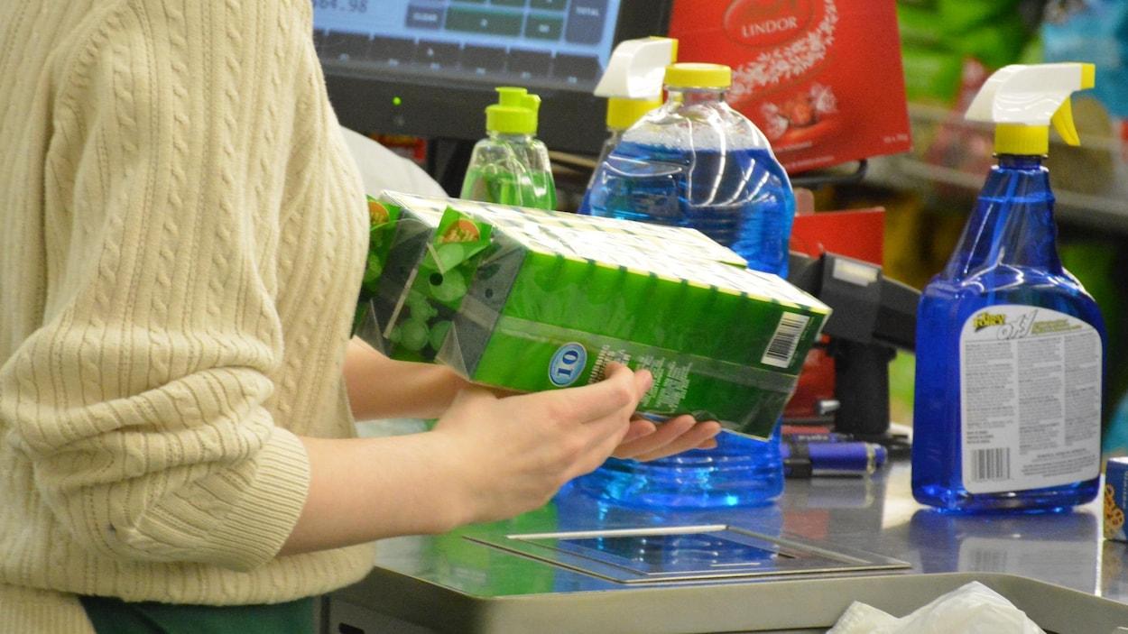 Une travailleuse à une caisse enregistre les achats de consommateurs.