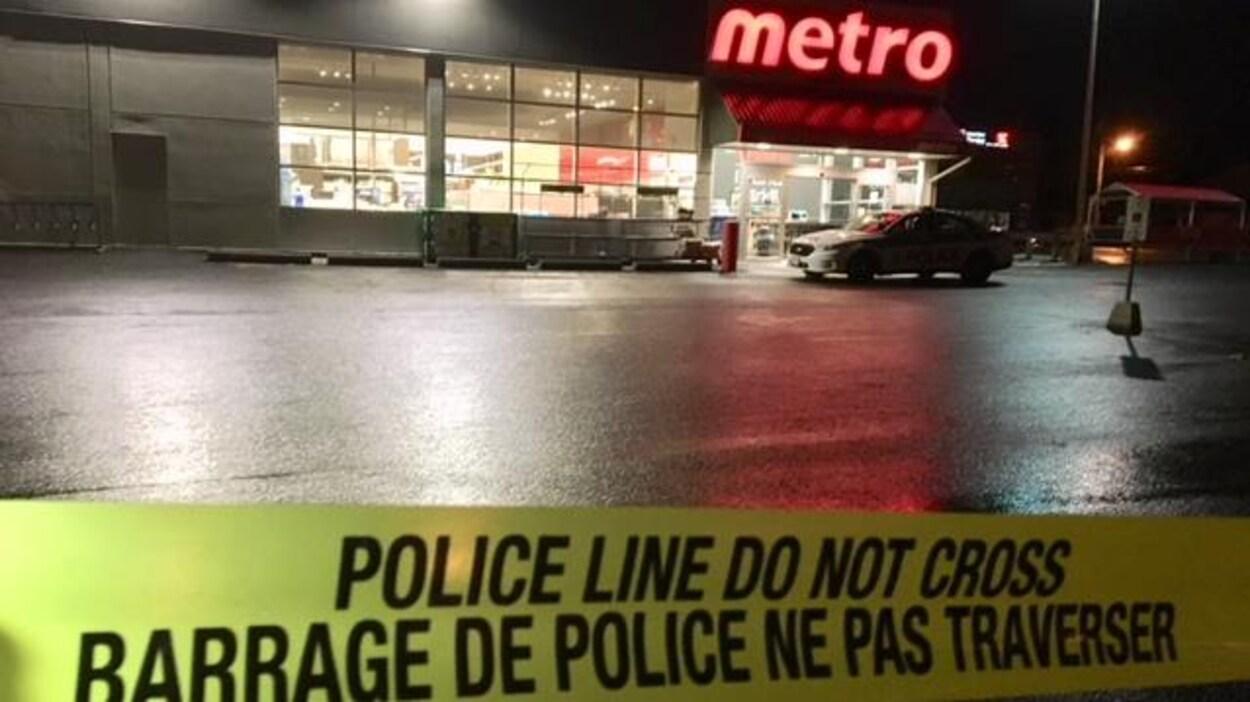 Un ruban jaune de barrage policier devant une voiture de police et une épicerie Metro.