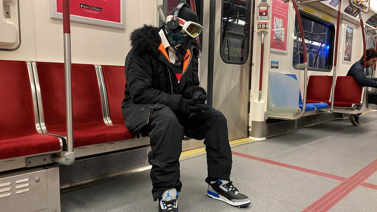 Un homme muni de lunettes de ski, d'une cagoule et de gants assis dans un wagon de métro.