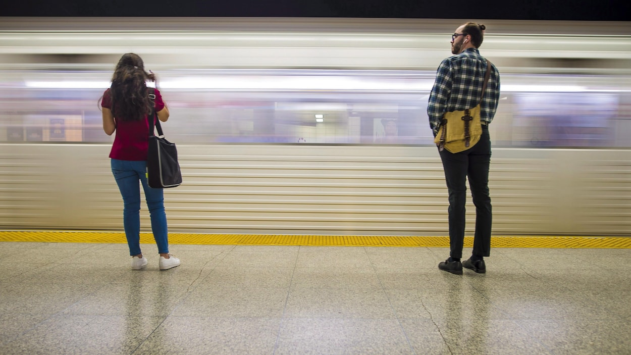 Une femme et un homme sur le quai devant une rame de métro en marche