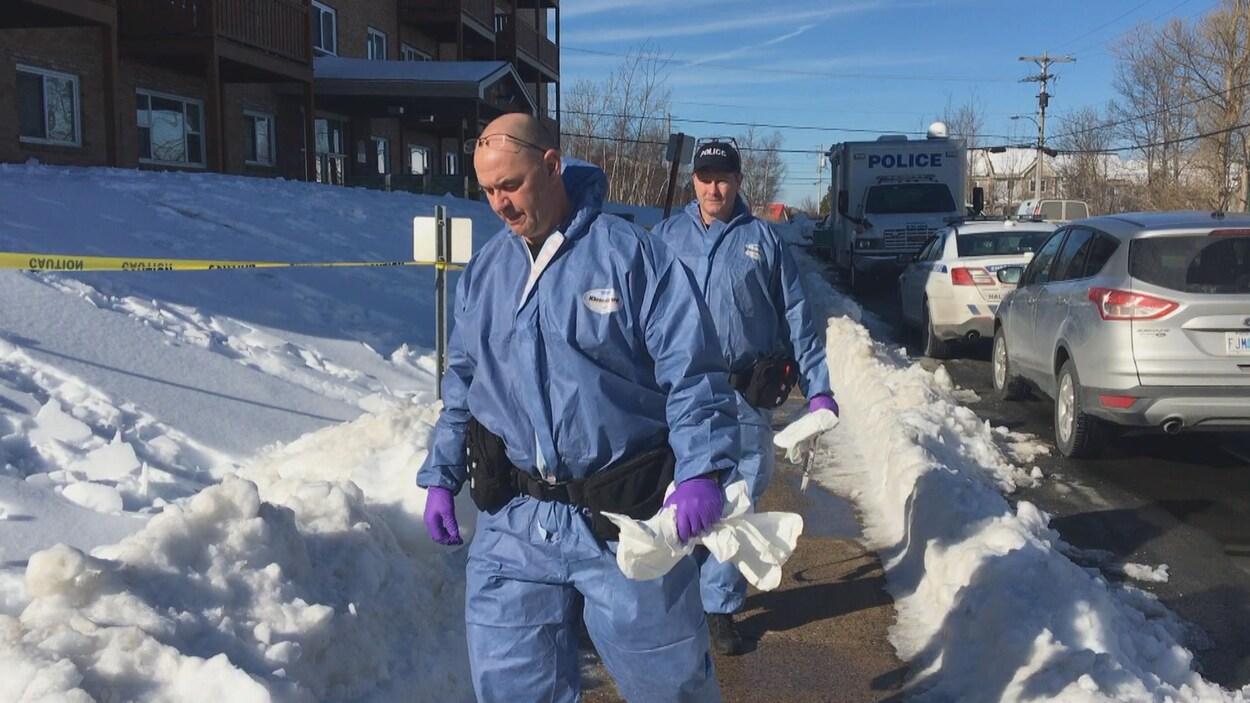 Des policiers vêtus de combinaisons bleues marchent sur le trottoir et entrent sur une scène de crime.