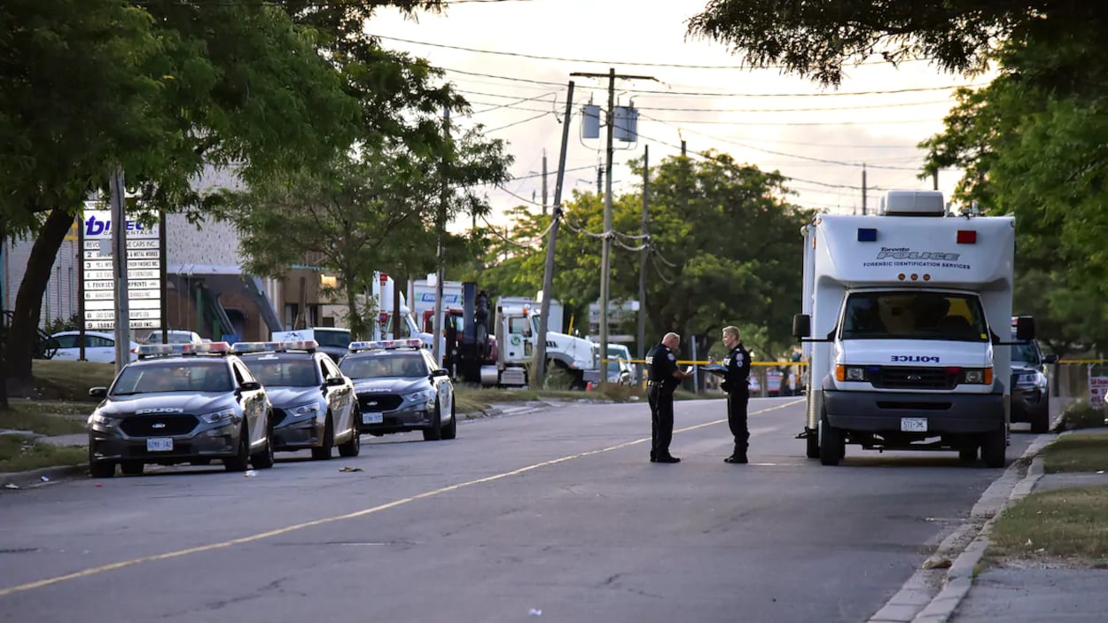 Deux agents discutent dans la rue près d'un véhicule de la police et d'autopatrouilles.
