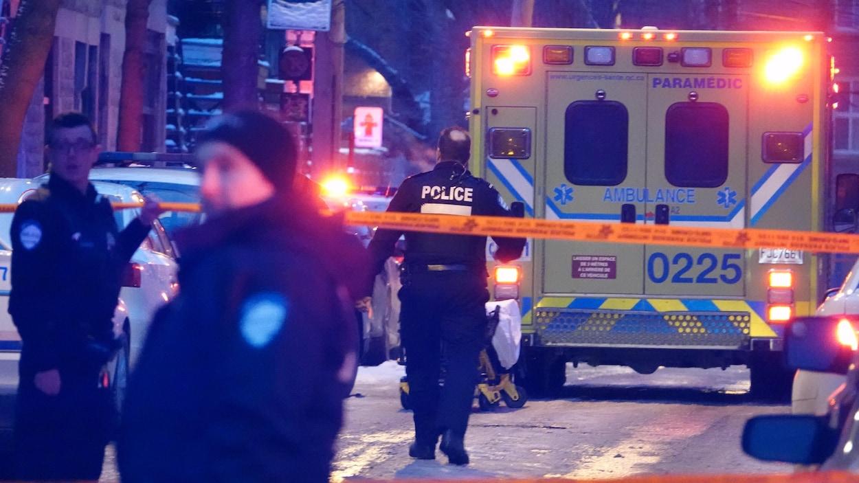 Un policier, vu de dos, marche dans la rue vers une ambulance.