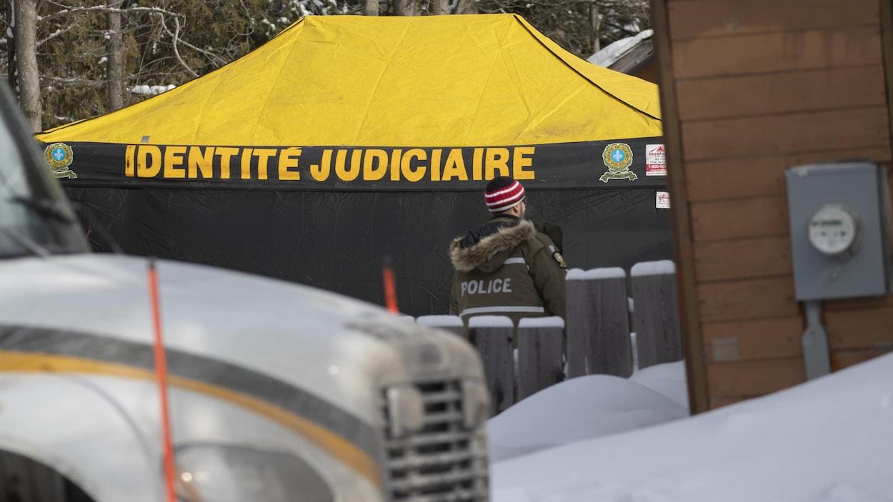 Un policier devant une tente de la SQ sur laquelle on peut lire «identité judiciaire».