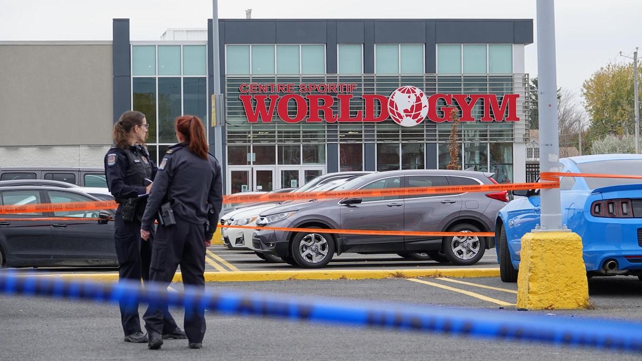 Deux policières discutent derrière un cordon de sécurité, dans un stationnement, devant la devanture du centre sportif World Gym.