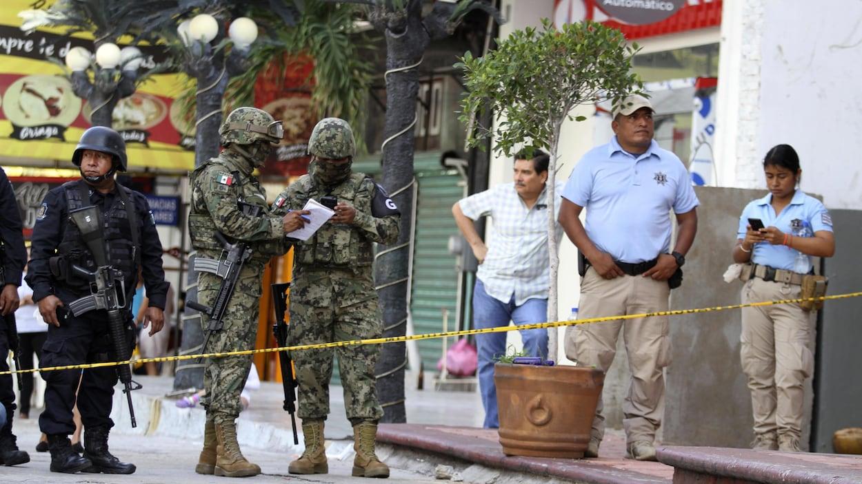 Des soldats de la Garde nationale ainsi que des officiers municipaux se tiennent dans un périmètre délimité par un cordon de sécurité.