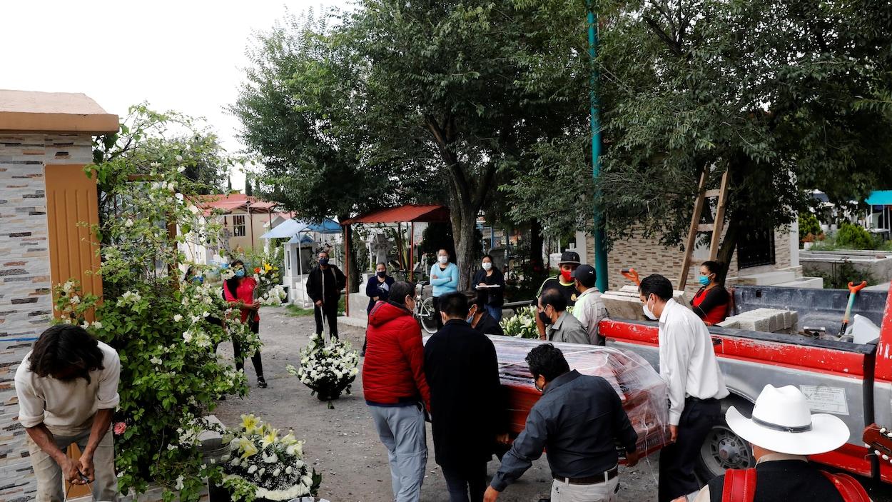 Des travailleurs de pompes funèbres transportent un cercueil d'une victime de la pandémie, à Mexico, la capitale du Mexique.