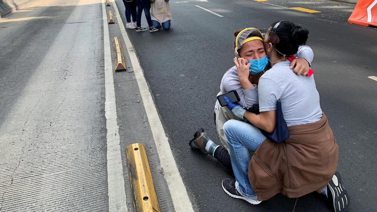 Une jeune femme pleure dans les bras d'une autre jeune femme, à genoux dans la rue.