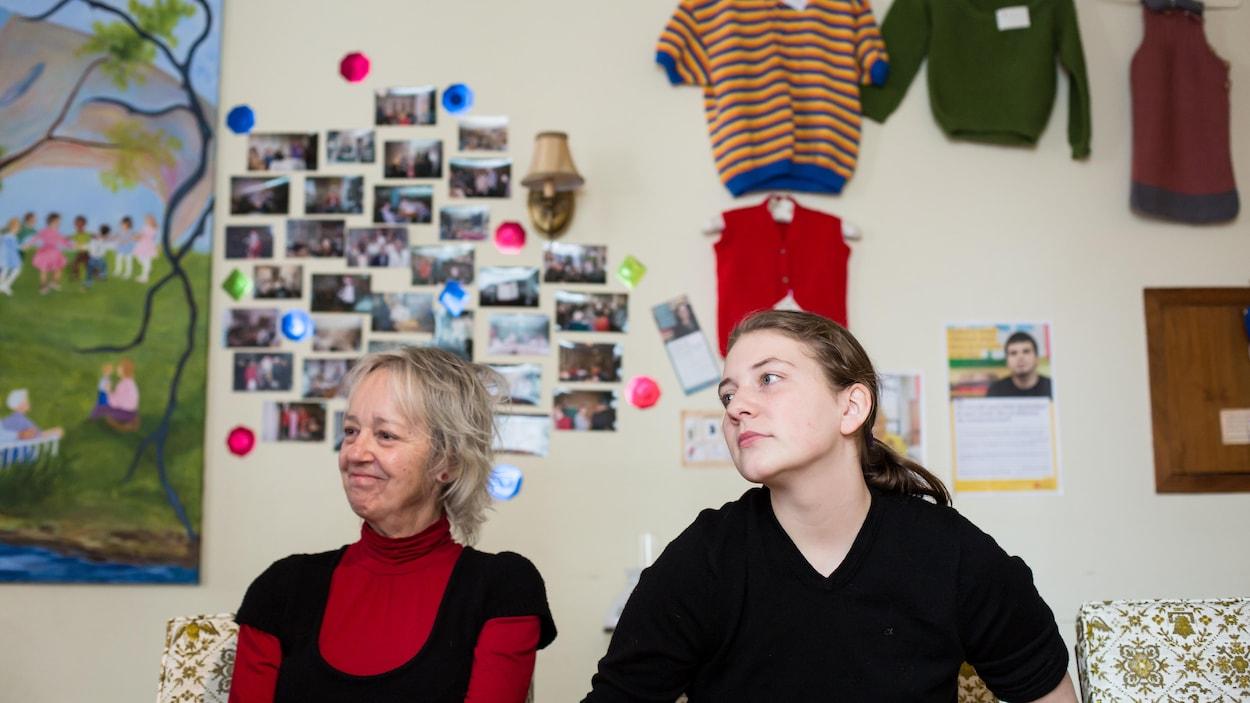L'aînée Suzanne Lavallée et l'adolescente Lydia De Melo sont assises côte-à-côte devant un mur orné de photos et de vêtements tricotés à la main.