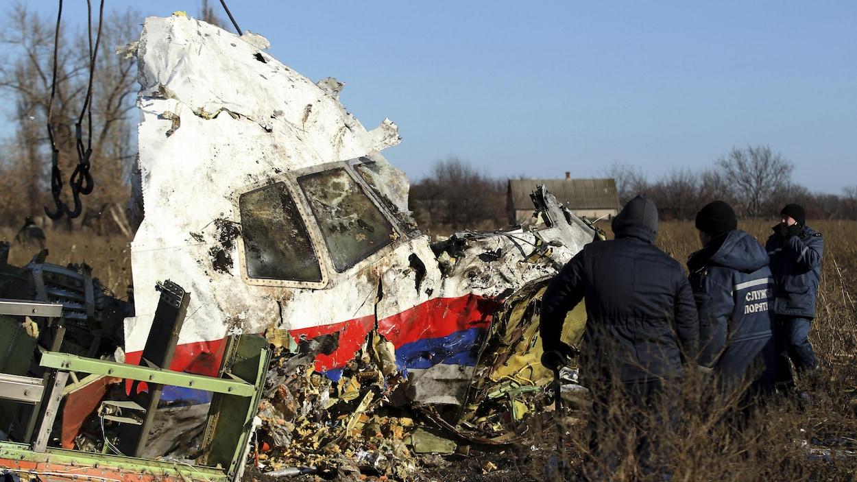 Des hommes inspectent la carcasse de l'avion.