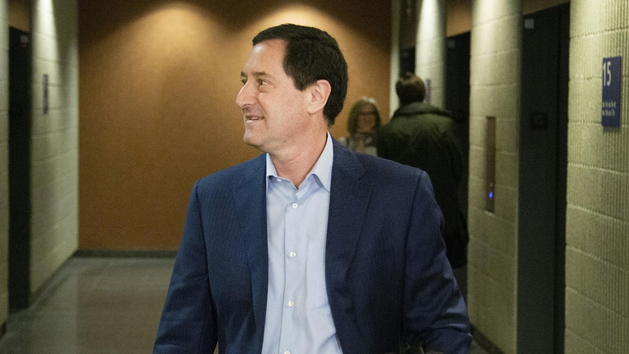 Un homme photographié de profil sourit dans un couloir avec, au fond, des ascenseurs devant lesquels attendent deux personnes.