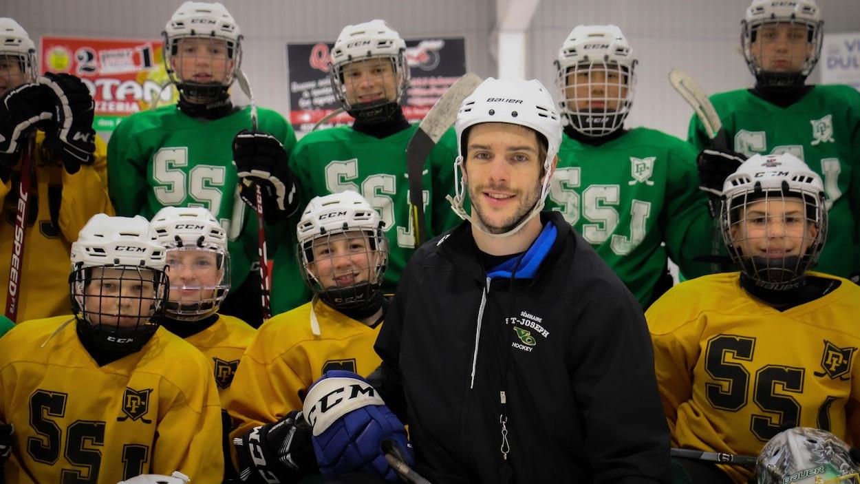 Un entraîneur de hockey devant des joueurs.