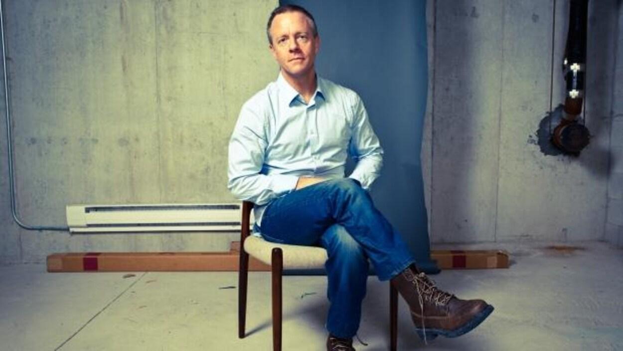Un portait de Michael Bryant assis sur une chaise. Il a une chemise bleue et des jeans et les jambes croisées