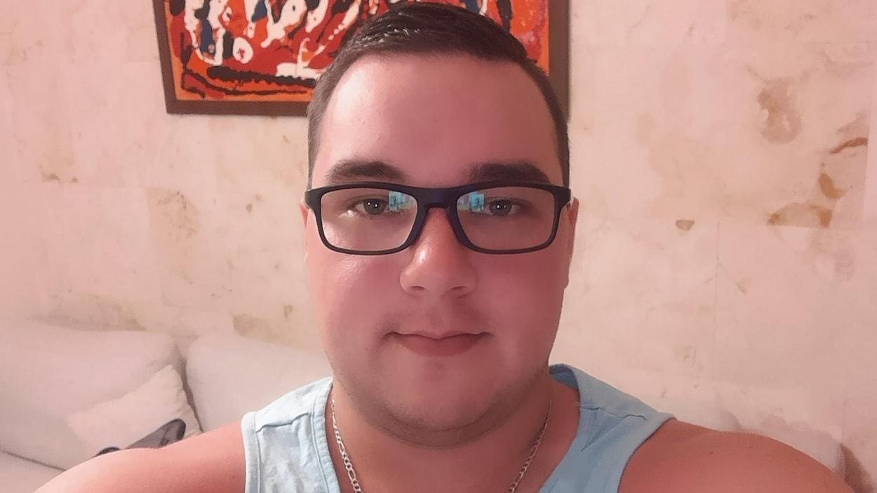 Photo de l'accusé portant des lunettes noires et une camisole bleue.