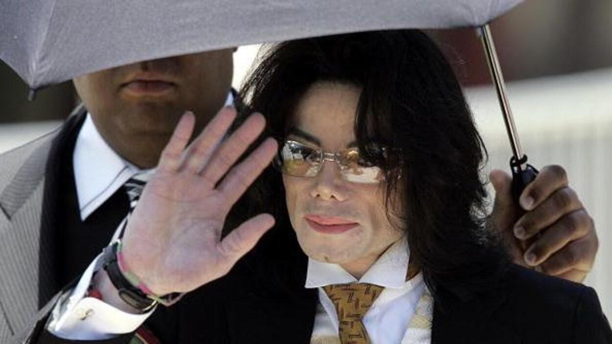 Michael Jackson, qui porte des lunettes, tente de protéger son visage avec sa main.