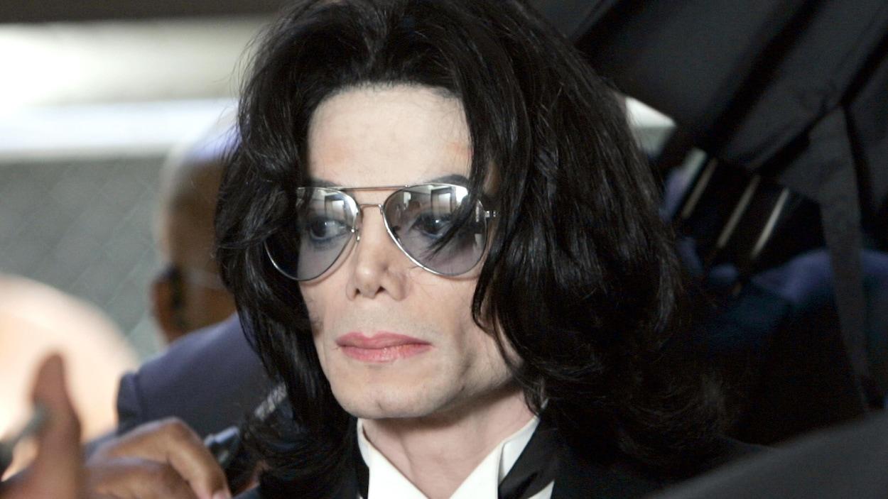 Le chanteur Michael Jackson, vêtu d'un complet noir et portant des verres fumés.