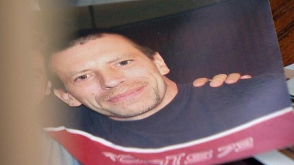 Une photographie de Michael MacIsaac qui le montre souriant, portant un  chandail rouge et bleu marine.