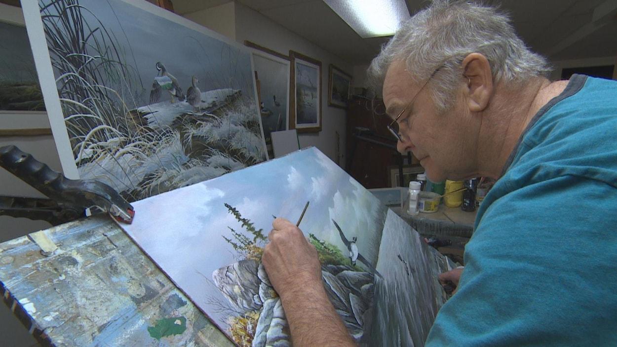 Un homme peint un paysage.