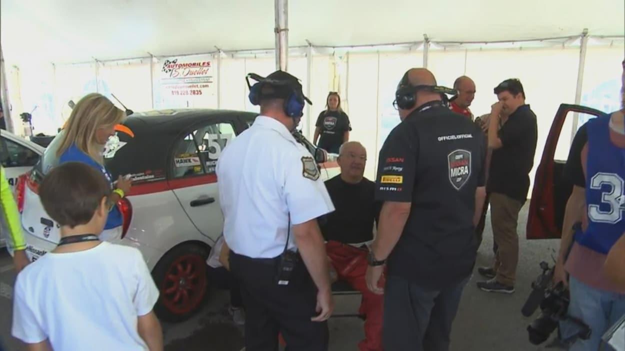 Des hommes, debout, entourent Michel Barrette et discutent avec lui alors qu'il est assis sur une chaise près de son véhicule de course.
