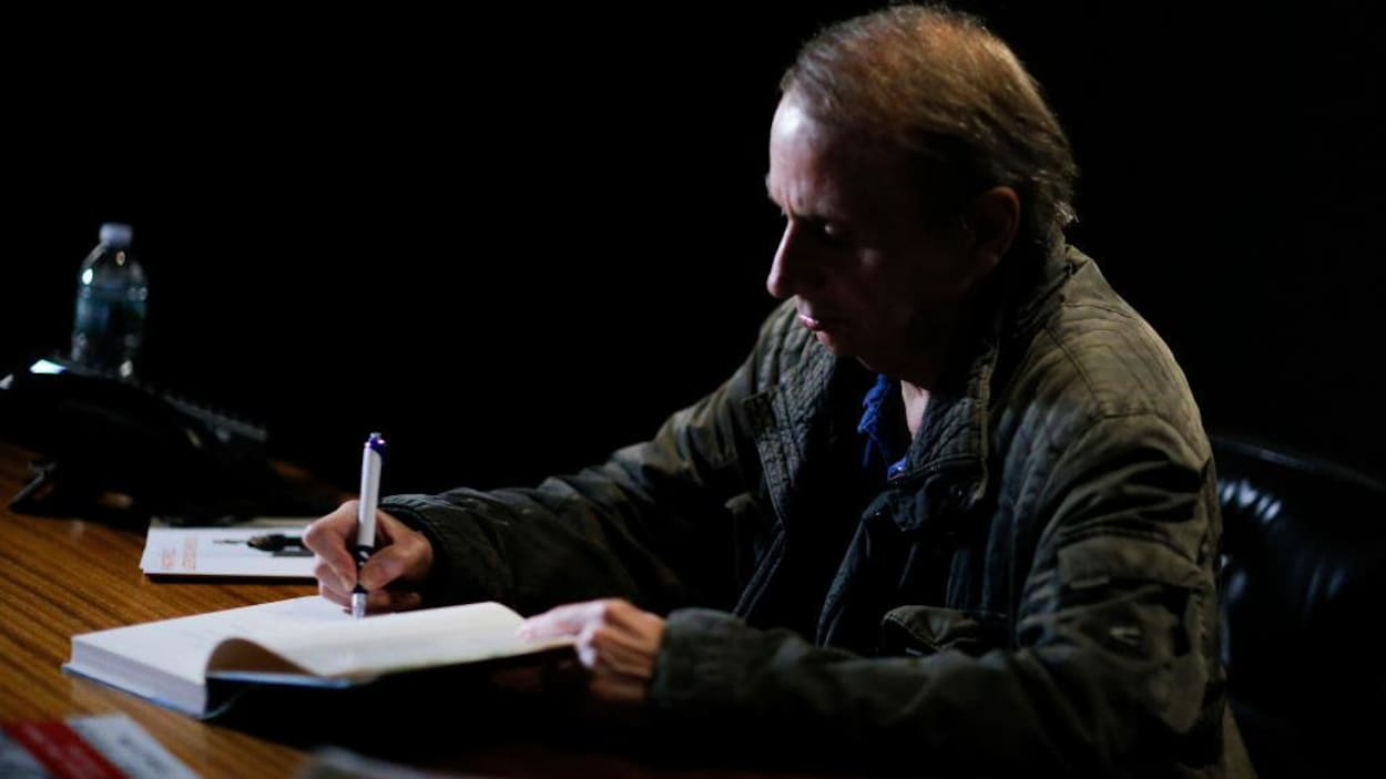 L'écrivain Michel Houellebecq signant un livre sur une table.