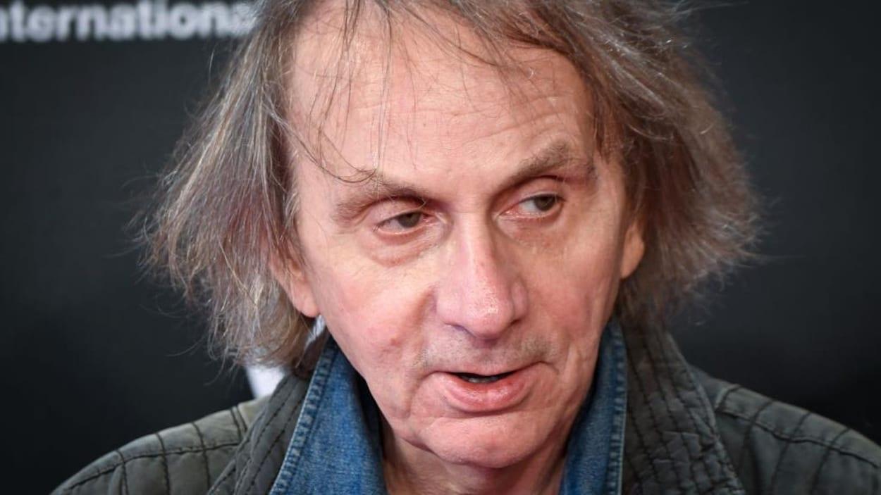 Michel Houellebecq porte une chemise en denim et une veste grise.