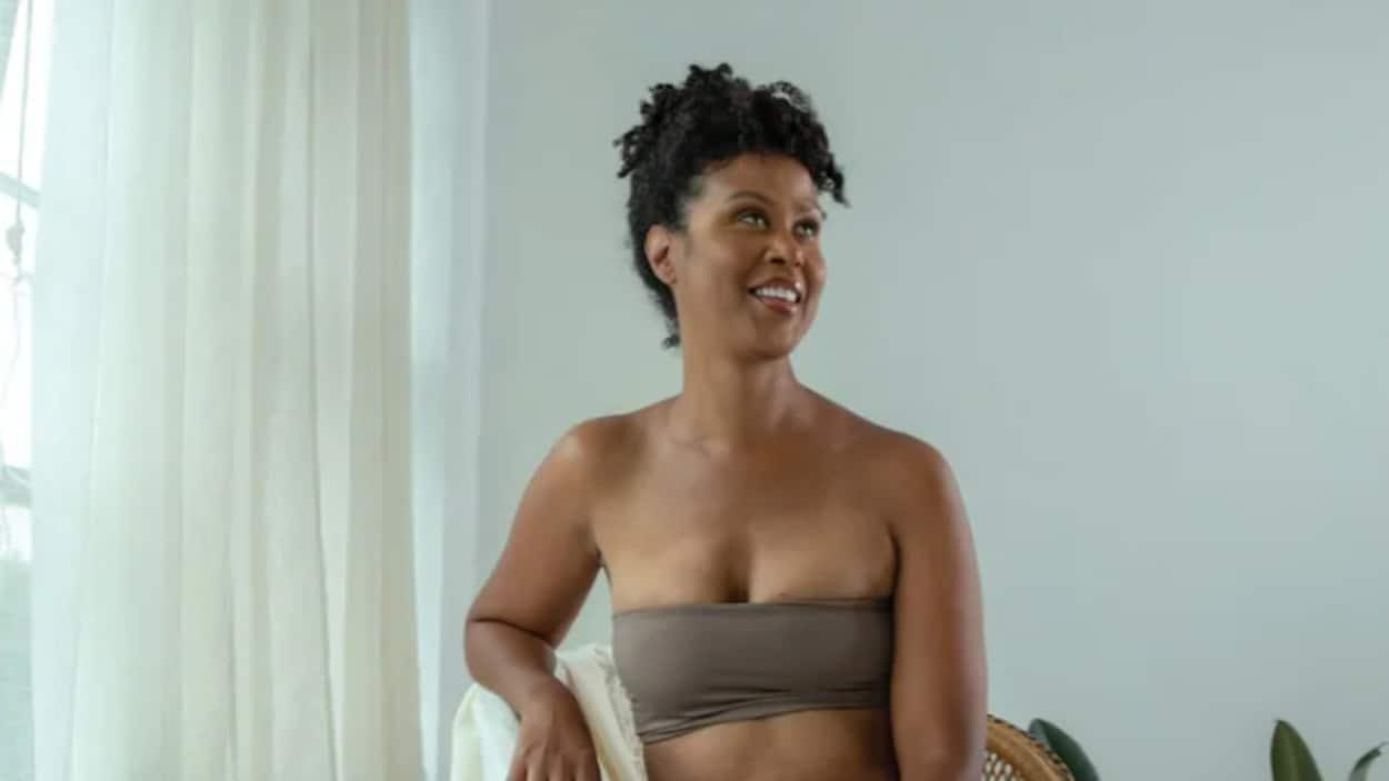 Une femme pose avec un bandeau sur la poitrine.