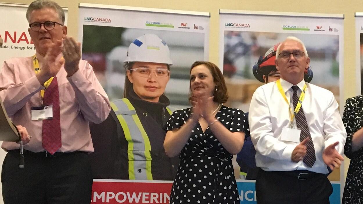 Une femme entourée de deux hommes à cravate applaudissant devant des affiches publicitaires