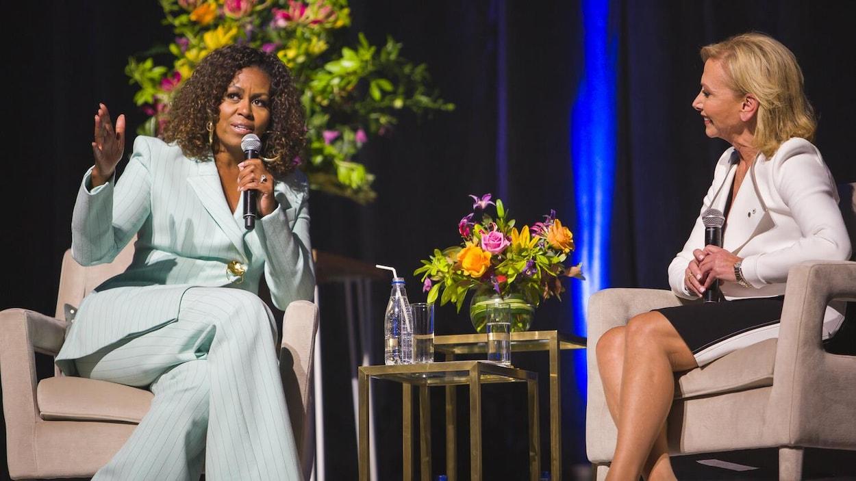 Michelle Obama sur une scène, assise avec un micro, aux côtés de Christiane Germain