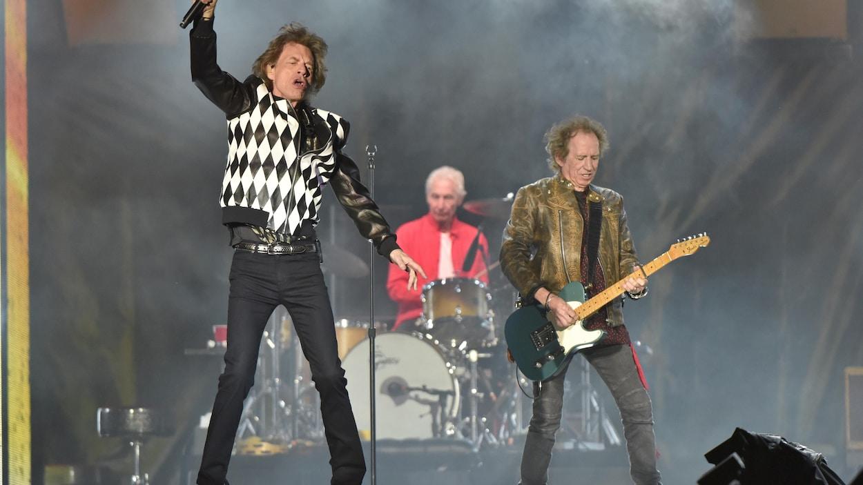 Un chanteur est accompagné d'un batteur et d'un guitariste sur scène.