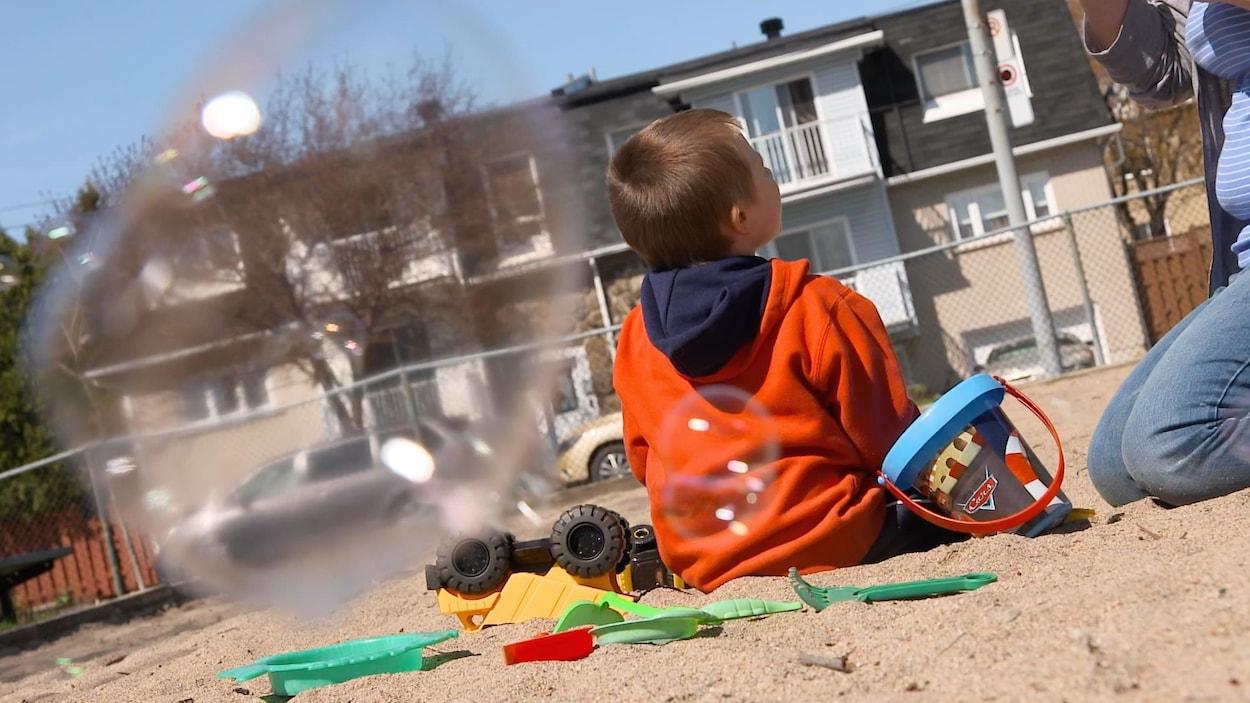 L'enfant est assis dans le sable, entouré de ses jouets.