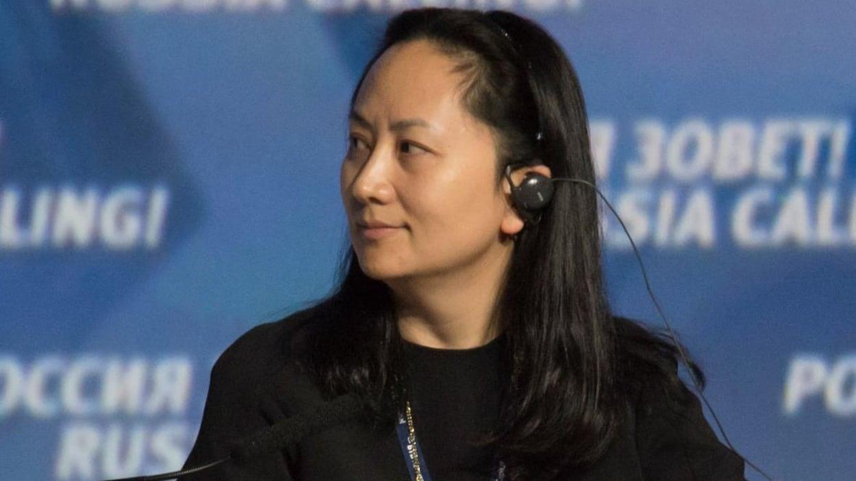 Meng Wanzhou porte une oreillette et regarde vers sa droite.