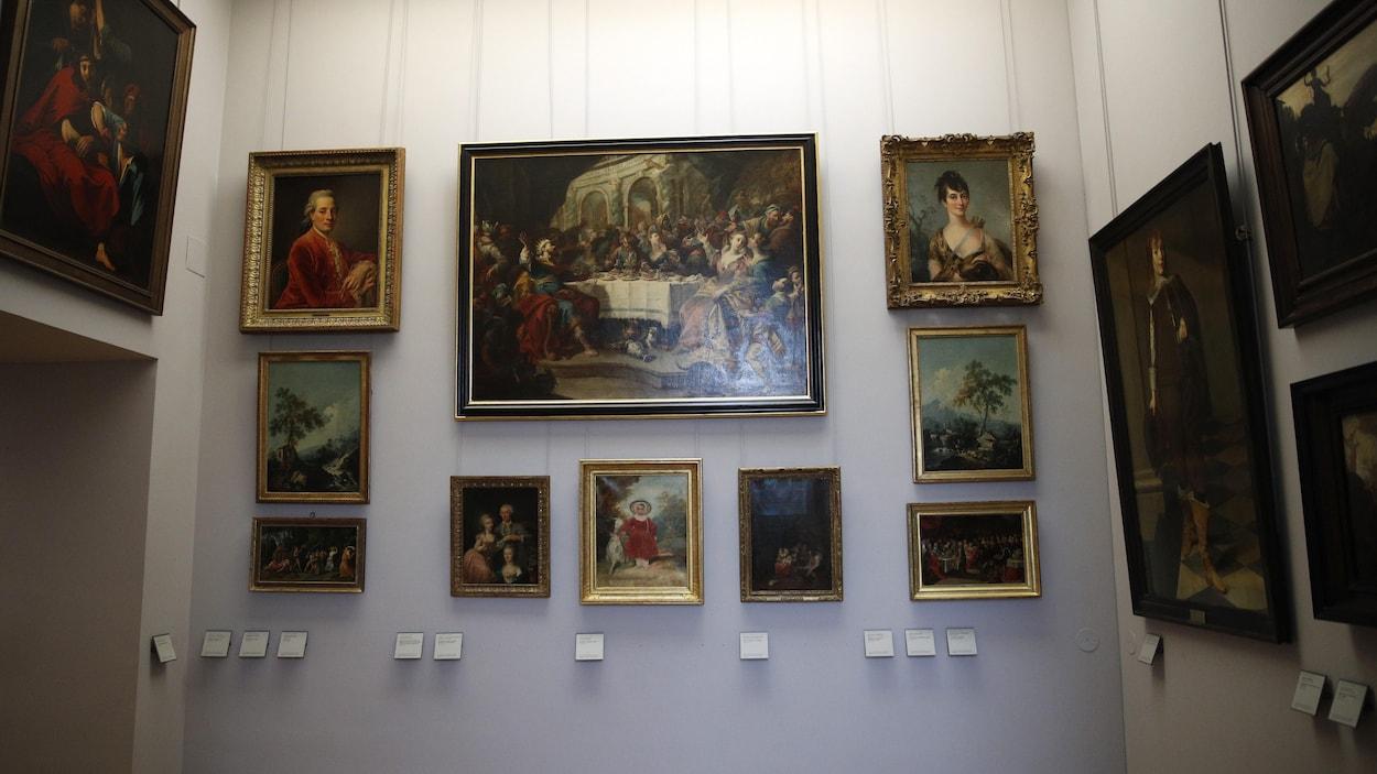 Plusieurs peintures de diverses tailles sont accrochées aux murs d'une salle du Louvre