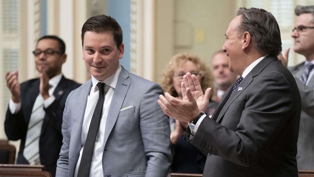 Simon Jolin-Barrette à l'Assemblée nationale le jeudi 28 mars 2019, avec François Legault, à sa droite, qui l'applaudit et d'autres députés qui font de même à l'arrière.