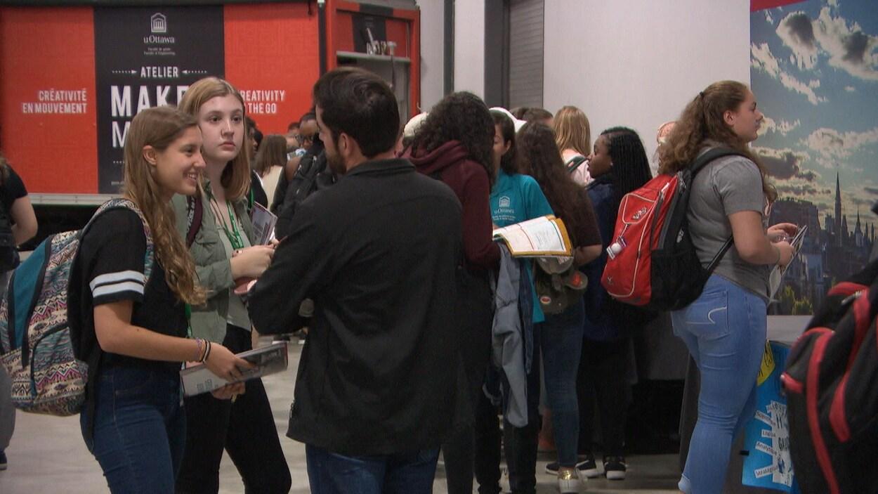 Des élèves discutent dans un salle avec des documents en main.