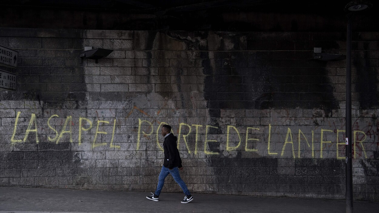 Un jeune homme marche près d'un mur où il est écrit : « La sapel porte de lanfer ».