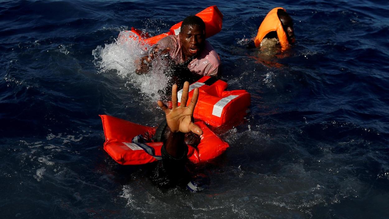 Des migrants tentent de rester à flot après être tombés de leur embarcation de fortune fabriqué en caoutchouc.