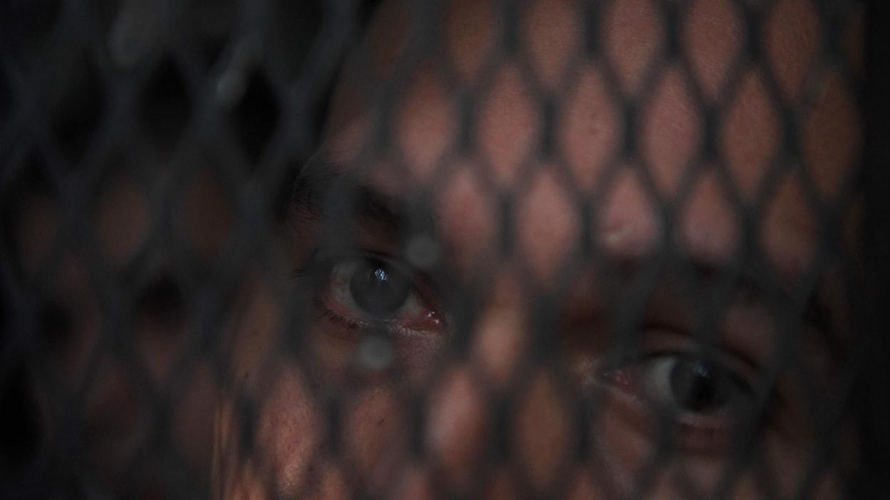 Un membre de la Mara Salvatrucha, alias MS-13, dont les yeux sont visibles derrière une grille dans un centre de détention au Salvador.