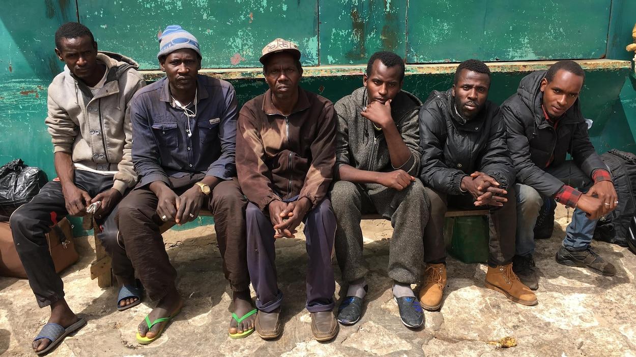 Six hommes assis côte à côte
